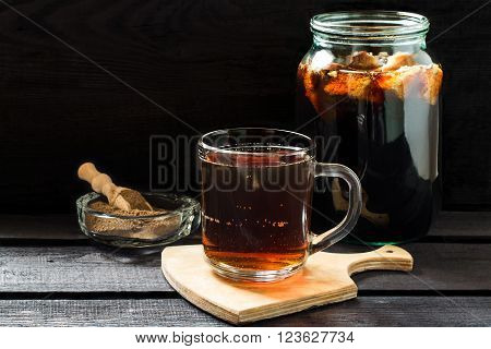 Traditional Russian drink kvass made from bread rye malt sugar and water. Kvass in the jar rye malt in a bowl with scoop on a dark wooden background. Selective focus