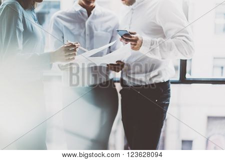 Business team meeting, work process.Photo professional crew working with new startup project.Project managers near window.Analyze business plans, smartphone hands. Blurred background, film effect.