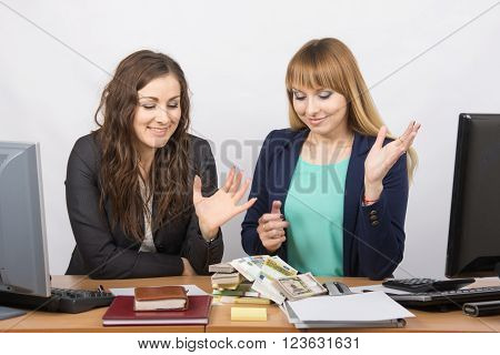 Two Office Employee Looking At A Lot Of Money On The Table