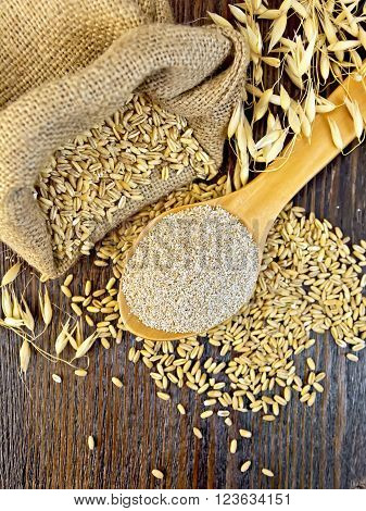Bran flakes oat in spoon, a bag of grain oats, oat ears on the background of the wooden planks on top