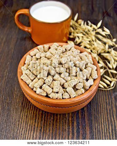 Oat bran large in earthenware bowl, a mug with milk, oat stalks on a wooden boards background