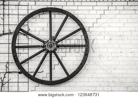 Old wheel hanging on a wall in black and white poster