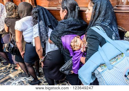 Antigua Guatemala - March 24 2016: Local women carry float (1 also her child dressed as penitent) in Holy Thursday procession in colonial town with most famous Holy Week celebrations in Latin America.
