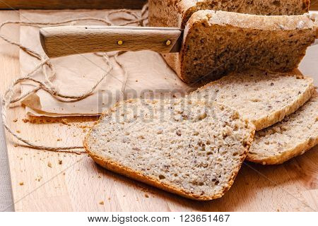 Food. Sliced whole wheat bread and knife on cutting board wooden background