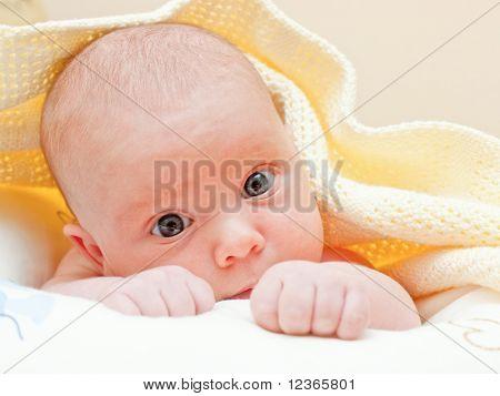Pasgeboren babymeisje liggen onder geel handdoek