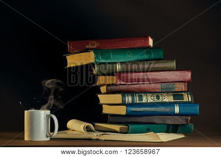 Old vintage books and white cup  on a dark background