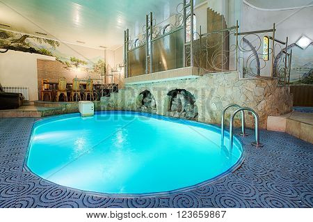 Blue swimming pool in modern spa interior. Resort and wellness. Blue clear water indoor pool in spa center. Healthcare and rest, relaxation concept.