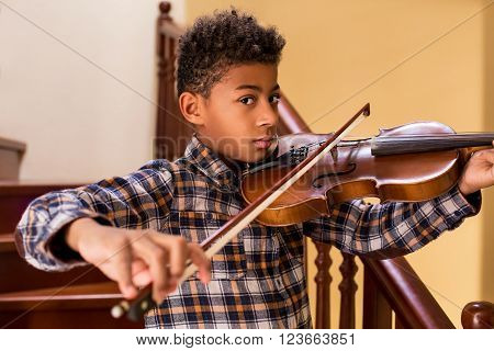 Black kid playing violin. Boy plays violin on stairs. High notes and beautiful sound. Young violinist's solo.