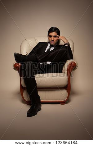 Confident successful young handsome man businessman in elegant suit with tie on armchair . Manhood. Male Beauty. Fashion model studio shoot . Italian Style