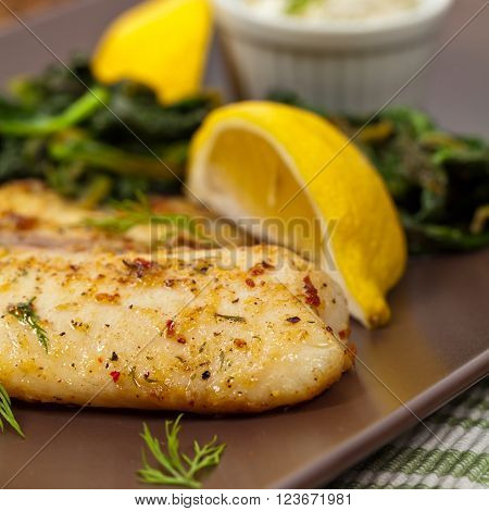 Baked Tilapia Fish with Sauteed Spinach. Selective focus. ** Note: Shallow depth of field