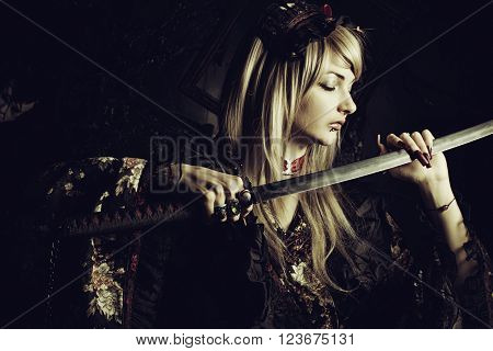 Cute samurai girl with katana posing over dark background