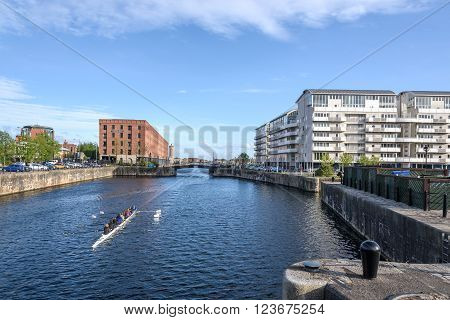 Women rowing through the Liverpool waterfront ,UK