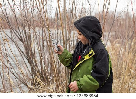 Child playing on handheld device taking videos outdoors.