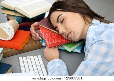 Young woman fell asleep while reading books at the table