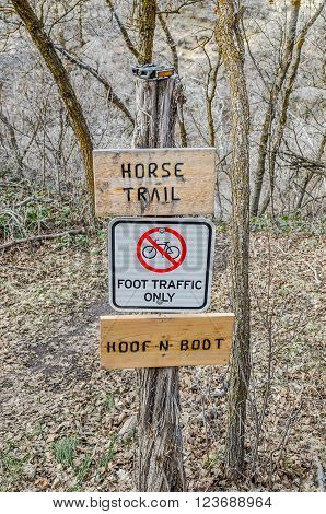 Trail sign for a horse trail with no bicycles allowed. Notice the upside down V instead of an A. See the bicycle pedal on top of the sign post.