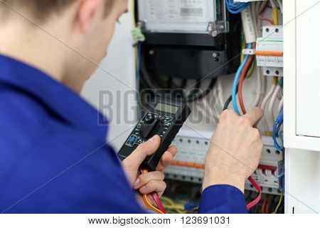 Young electrician measuring voltage in fuse board poster
