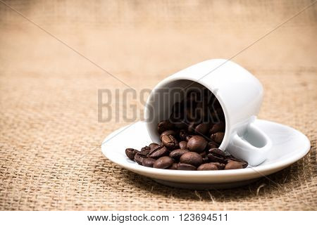 White coffeecup and plate with spilled coffeebeans on gunny textile