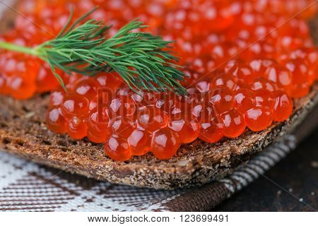 pumpernickel with salmon roe on rustic background