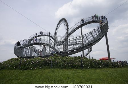Duisburg, Germany - May 18, 2015: Tiger and Turtle Roller coaster magic Mountain with people visiting it. This sculpture is an art installation and landmark in Angerpark Duisburg 