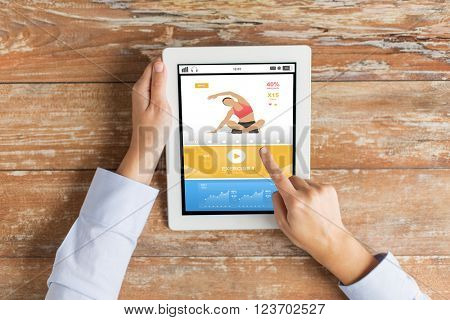 sport, fitness, people and technology concept - close up of female hands pointing finger to tablet pc computer with sports application on screen