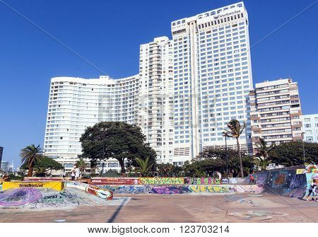 DURBAN SOUTH AFRICA - MARCH 23 2016: Many unknown children boarding on skate board park in front of residential and commercial buildings on beachfront in Durban South Africa