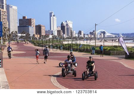 DURBAN SOUTH AFRICA - MARCH 23 2016: Many unknown people walk and ride along paved promenade on Golden Mile beachfront against city skyline in Durban South Africa