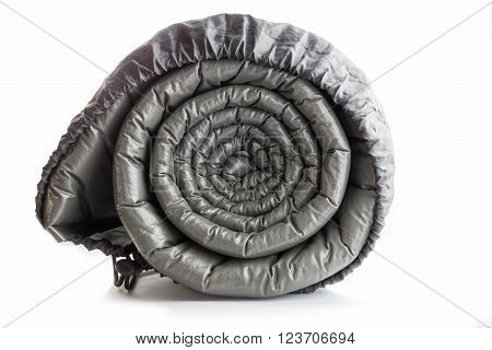 Gray plastic air camping mattress rolled in the back isolated on white background