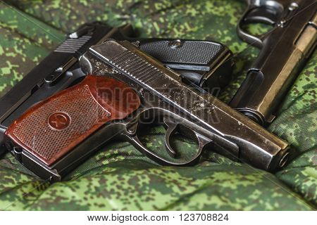 Weathered generic russian soviet semi-automatic 9mm pistols on pixel camouflage background