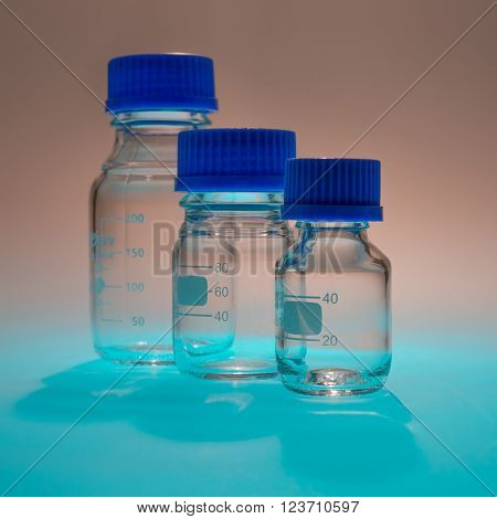 Glass laboratory apparatus isolated on blue table with brown background