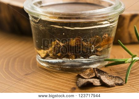 Sliced Black Truffle In Olive Oil In Small Jar And Fresh Rosemary