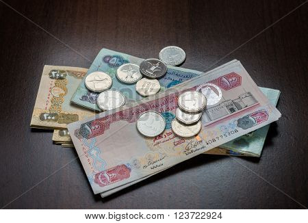 Assorted UAE Dirham currency notes and coins on dark background.