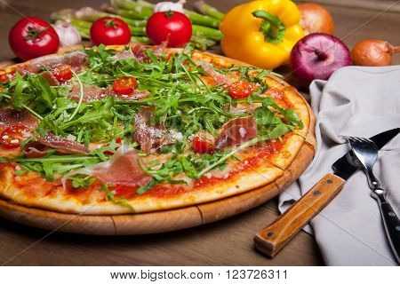 pizza with ham, cheese, and pizza ingredients on the table. decorated with arugula