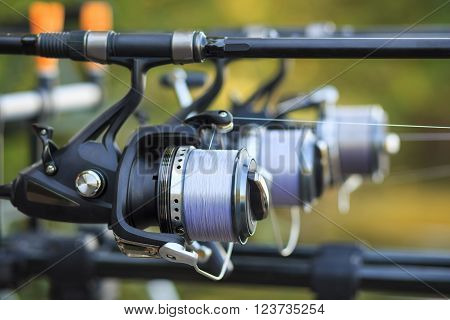 Three Fishing Rods With Reel Set Up On Holder