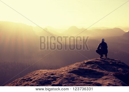 Young man in black sportswear sit on cliff edge and look into red Sun at horizon over misty valley