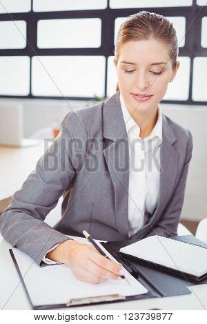 Close-up of beautiful businesswoman writing on notepad at desk in office