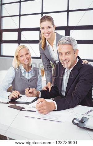 Portrait of happy business people with client at desk in meeting room