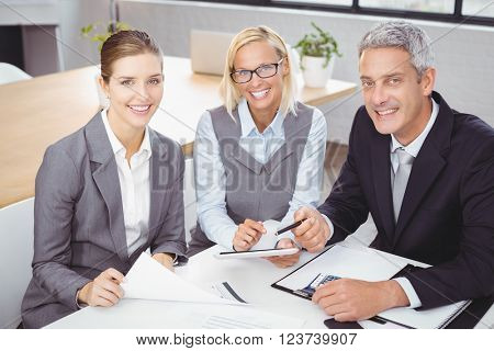 Portrait of business people smiling while sitting with client in meeting room