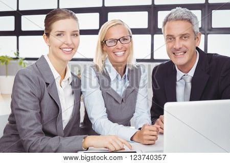 Portrait of happy business people with laptop at desk during meeting