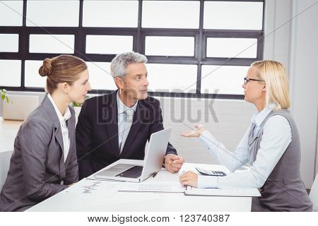 Business people discussing with client at desk in office