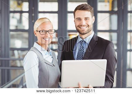 Portrait of happy business people with laptop standing in office
