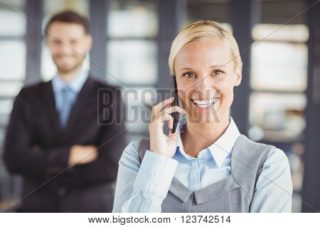 Happy businesswoman talking on mobile phone while male colleague in background