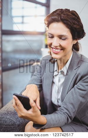 Close-up of businesswoman smiling while looking at mobile phone
