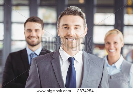 Portrait of happy business people wearing suit standing in office