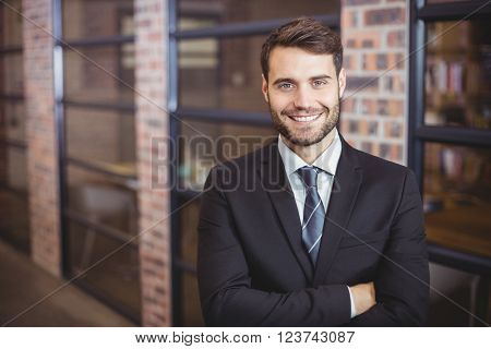 Portrait of happy handsome businessman with arms crossed standing in office
