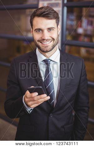 Portrait of happy businessman using cellphone in office