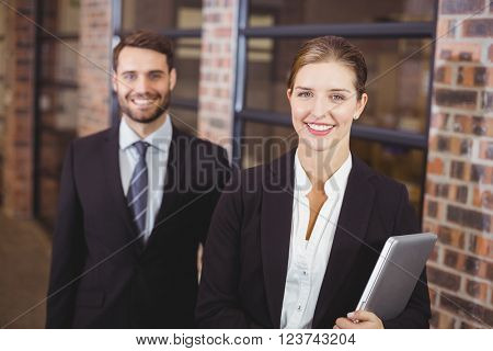 Portrait of happy businesswoman standing with male colleague in office