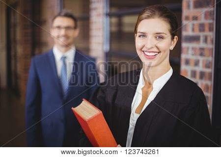 Portrait of happy female lawyer with businessman standing in background