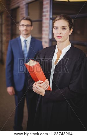 Portrait of confident female lawyer with businessman standing in background at office