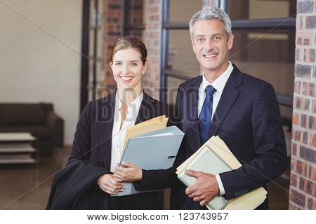 Portrait of happy business people with files standing by window at office