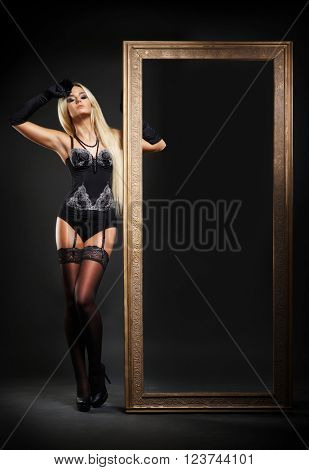 Sexy lady in erotic lingerie standing with a frame.